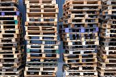Stacks Of Colorful Rough Wooden Pallets At Warehouse In Industrial Yard. Pallets Background. Cargo A poster