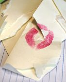 stock photo of loveless  - Broken relationship is illustrated with this torn envelope with lipstick smudge - JPG