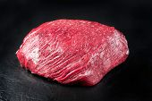Raw dry aged wagyu thick flanch knuckle as closeup on black background with copy space  poster
