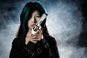 pic of asian woman  - Asian beauty holding gun with smoke in background - JPG