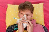 sehr krank Mann legt während bläst seine Nase in seinem Bett mit warmen Wasser Flasche und thermometer