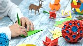 Man At Origami Folding Lesson. Collection Of Beautiful Origami Figurines On Wooden Table. Traditiona poster