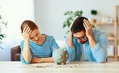 Financial Planning  Bankrupt Family Couple  In Stress With Piggy Bank At Home poster