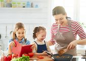 Healthy food at home. Happy family in the kitchen. Mother and children daughters are preparing veget poster