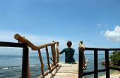 A Young Lady, Sitting On The Wooden Bridge Facing The Ocean View, Enjoying The Solitude, Be Free In  poster