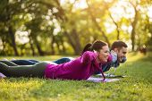 Couple Is Exercising In Park. Exercise For Sciatica Recovery. poster