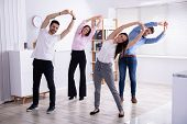 Group Of Happy Young Businesspeople Doing Stretching Exercise In Office poster