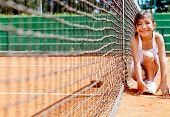 stock photo of caddy  - Cute ball girl at the tennis court smiling - JPG