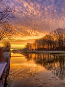 Colorful And Dramatic Sunrise Or Sunset Over A River Or Canal Landscape poster