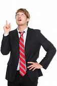 Businessman having an idea - eureka. Thinking young business man pointing up in suit isolated on whi