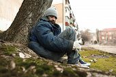 Poor Homeless Man Sitting On Ground Outdoors poster