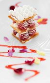 Slice of mille-feuille cake with raspberries and sweet sauce on porcelain plate