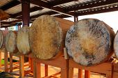 Buddhist Drums Laying On Wooden Tables Displaying At The Cultural Park - Traditional And Cultural Pr poster