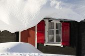 Swiss Chalet With Red Shutters In Deep Snow
