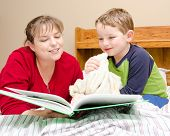 Mother reads bedtime story to young boy in his room at night