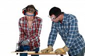 Tradespeople cutting a wooden plank with a circular saw