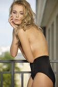 Beautiful slim sexy young blonde woman in balcony