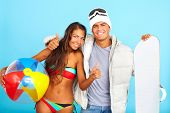 Portrait of happy girl in bikini with ball and handsome man in winterwear holding snowboard showing thumbs up and looking at camera