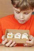 Boy in orange t-shirt look at open box of corrugated cardboard with cookies with almonds and icing sugar