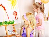 Little girl painting at easel in school. Education.