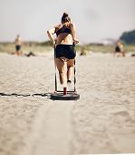 stock photo of sled  - Woman Pulling Crossfit Sled on a Beach - JPG