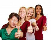 Equipe de mulheres multiculturais segurando seus polegares a sorrir