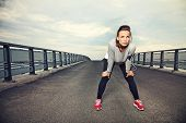 stock photo of jogger  - Focused runner outdoors resting on the bridge - JPG