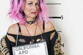 Portrait of senior punk woman making a face during mug shot