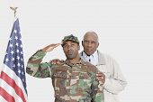 Portrait of father with US Marine Corps soldier saluting American flag over gray background