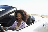 Portrait of smiling African American woman driving convertible on desert road