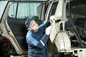 stock photo of peen  - Young auto mechanic worker repair flatten and align metal car body in automotive industry - JPG