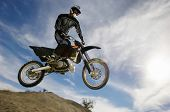 stock photo of motocross  - Low angle view of motocross racer in midair against cloudy sky - JPG