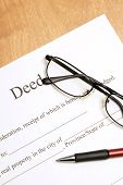 picture of deed  - A closeup shot of deed papers and glasses to read the fine print - JPG