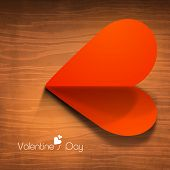 Happy Valentines Day concept with red fold paper heart on wooden background.
