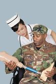 stock photo of artificial limb  - Nurse with US Marine Corps soldier holding artificial limb as he sits in wheelchair over light blue background - JPG