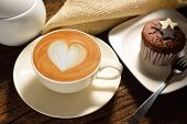 stock photo of latte  - A cup of cafe latte and cake on wooden background - JPG