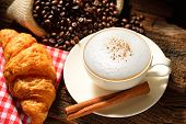 picture of croissant  - A cup of cappuccino with coffee beans and croissant - JPG
