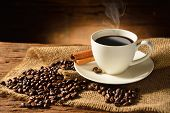 stock photo of coffee crop  - Coffee cup and coffee beans on old wooden background - JPG