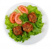 Tasty meatballs at plate with vegetables, isolated over white
