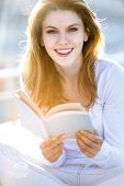 Lovely young woman holding a book