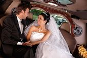 Happy young couple sitting in limousine on wedding day.