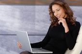 Beautiful ethnic female using laptop computer, smiling.