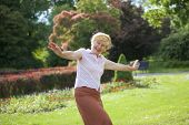 Gaiety. Delighted Playful Mature Woman With Outstretched Arms Laughing Outside
