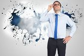 Thinking businessman tilting glasses against splash on wall revealing clouds