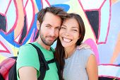 Happy couple selfie selfportrait in front of Berlin Wall, Berlin, Germany. Beautiful young interraci