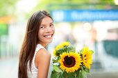 Woman holding sunflower flower smiling happy outdoor on beautiful summer day. Joyful multiracial Asian Caucasian female model in Kurfurstendamm, Berlin, Germany, Europe.