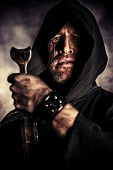 foto of sword  - Portrait of a courageous warrior wanderer in a black cloak and sword in hand - JPG
