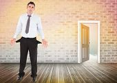 Businessman with empty pockets against door opening showing blue sky