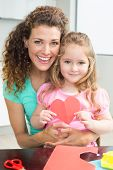 Cute little girl showing paper heart sitting on mothers lap at home in kitchen