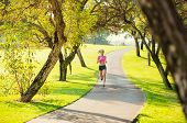 Attractive young woman jogging on Park Trail in the Early Morning.  Healthy Lifestyle Fitness Running Concept
